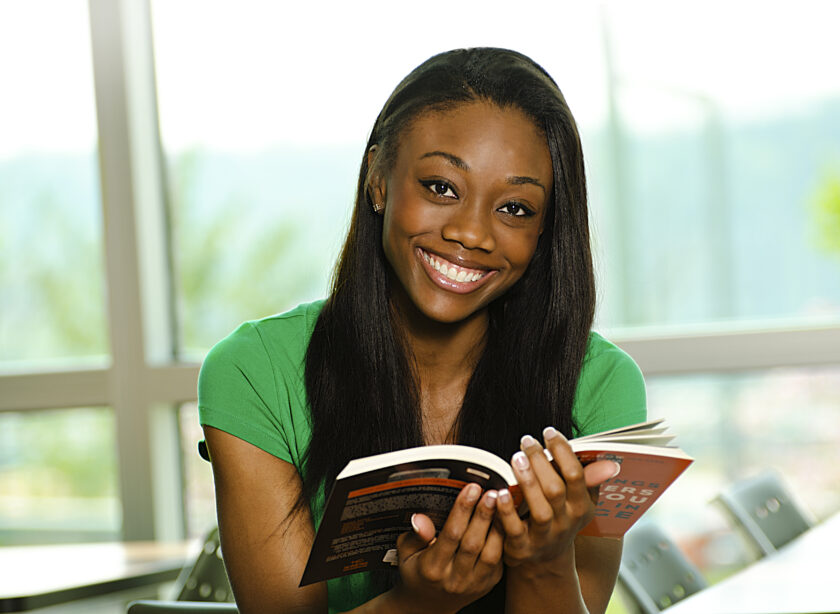 Girl smiling while holding a book
